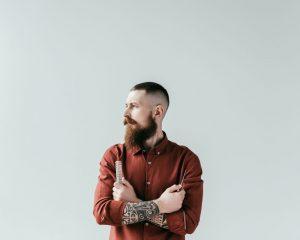 A self-employed barber wearing burgundy shirt