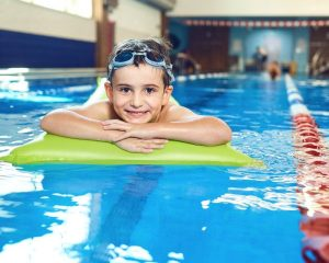 child using a swimming pool in a leisure centre and a lifeguard in the background