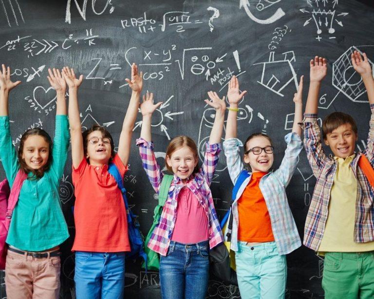 Kids standing in front of a black board in a school