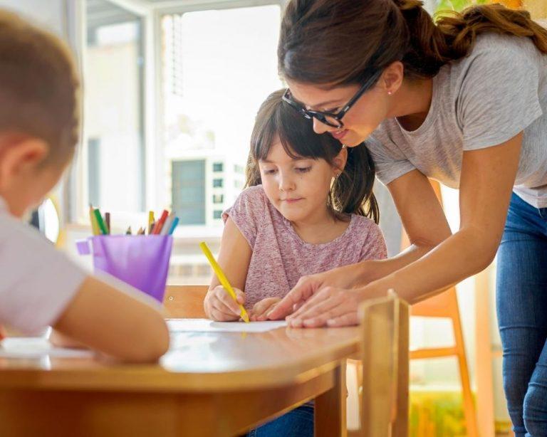 A teacher helping a student draw